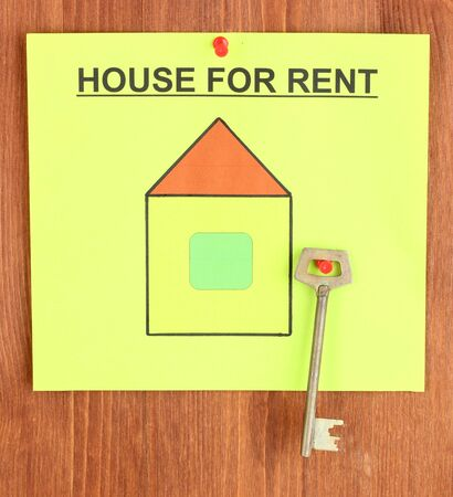poster about renting the house with the key on wooden background photo