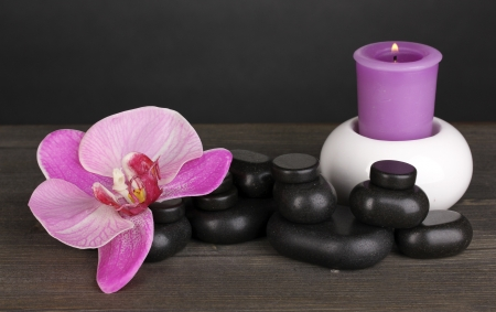 Spa stones with orchid flower and candle on wooden table on grey background photo