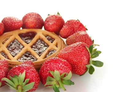 Tart garnished with strawberry on white background close-up photo