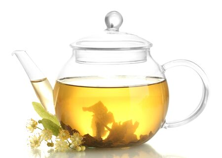 teapot of linden tea and flowers isolated on white photo