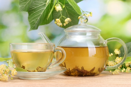 teapot and cup with linden tea and flowers on wooden table in garden Stock Photo - 14745337