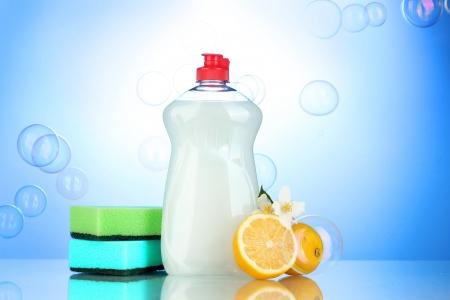 lavar platos: Lavavajillas l�quido con esponjas y lim�n con flores sobre fondo azul