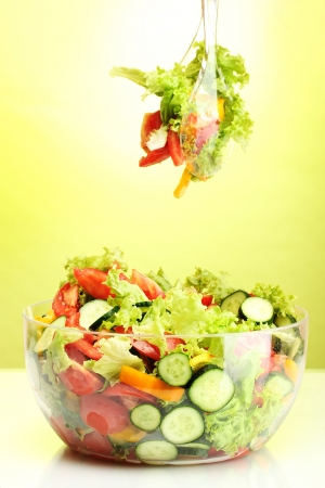 fresh vegetable salad in transparent bowl with spoon and fork on green background photo