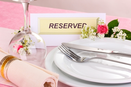 Table setting with reserved card in restaurant photo