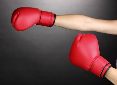 Red boxing gloves on hands on grey background photo