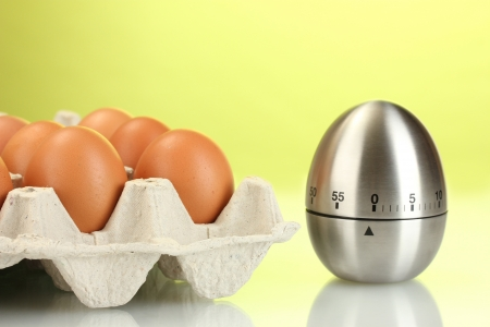 eggs in box and egg timer on green background Stock Photo - 14744462