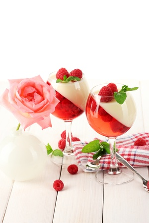 fruit jelly with raspberries in glasses on wooden table photo