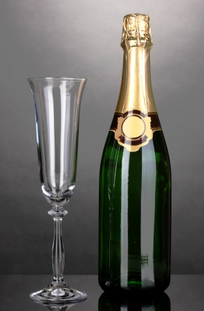 gold capped: Bottle of champagne and goblet on grey background Stock Photo