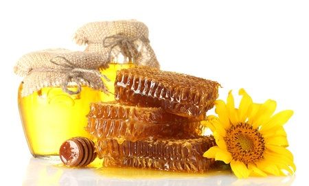 sweet honeycombs, jars with honey, wooden drizzler and sunflower, isolated on white photo