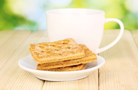 Cup of tea and cookies on wooden table on bright background photo