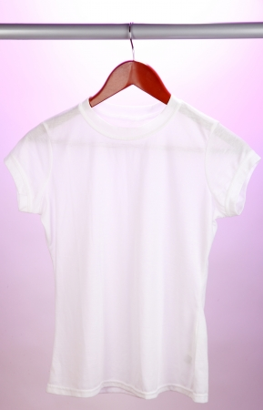 White t-shirt on hanger on pink background photo