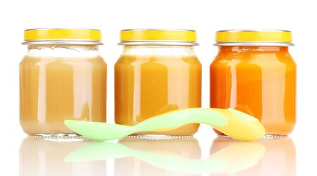 Jars of baby puree and spoon isolated on white photo