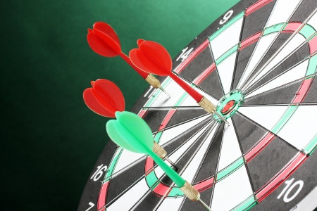 dart board with darts on green background Stock Photo - 14745259