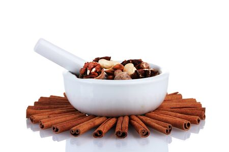 Composition of mortar with nuts and cinnamon isolated on white photo