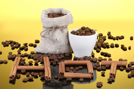Composition of canvas sack and the cup with coffee beans on bright background. Hot. photo