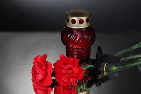 Memory lantern with candle,  carnations and black ribbon on grey background photo