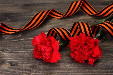 carnations and St. Georges ribbon on grey wooden background photo