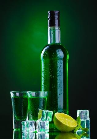 Bouteille et des verres d'absinthe avec de la chaux et de la glace sur fond vert Banque d'images - 14746078