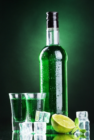 bottle and glasses of absinthe with lime and ice on green background photo