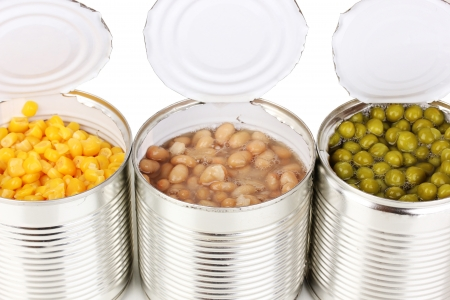 Open tin cans of corn, beans and peas isolated on white photo