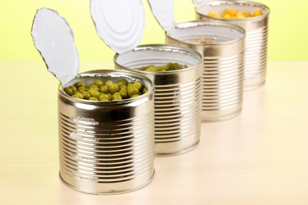 Open tin cans of peas, corn, bean and french bean on wooden table on green background Stock Photo - 14745113
