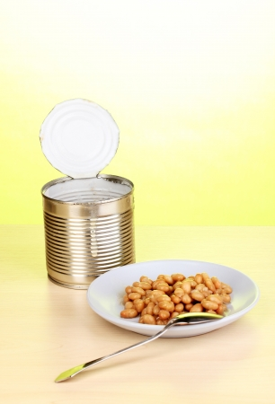 tinned: Open tin can and plate with bean and spoon on wooden table on green background
