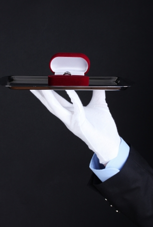 Mans hand holding ring in box on tray photo