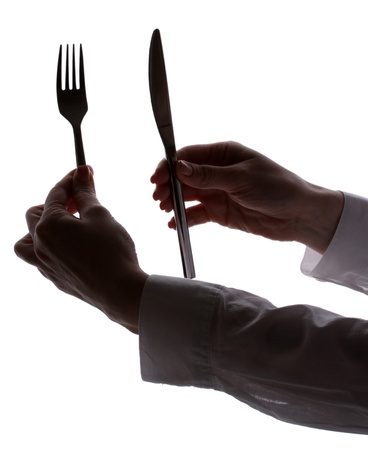 silhouette of womans hands with fork and knife isolated on white photo
