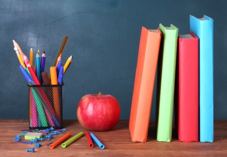 school desk: Composition of books, stationery and an apple on the teachers desk in the background of the blackboard Stock Photo