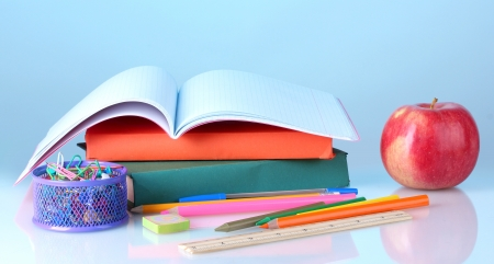 Composition of books, stationery and an apple  on colorful background photo