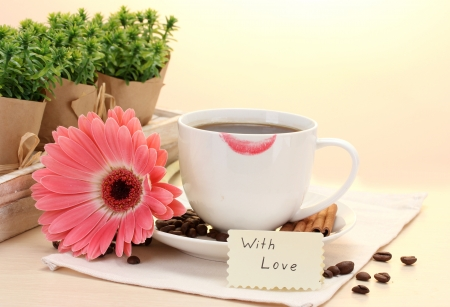 cup of coffee with lipstick mark and gerbera beans, cinnamon sticks on wooden table Stock Photo - 14738971
