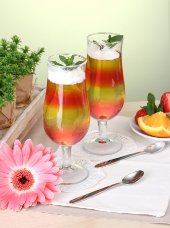 fruit jelly in glasses and fruits on table in cafe photo