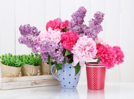spring flowers in cups on table on white wooden background photo