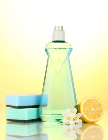 Dishwashing liquid with sponges and lemon with flowers on yellow background photo