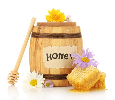 Sweet honey in barrel with honeycomb, wooden drizzler and flowers isolated on white photo