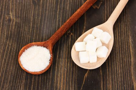 White sugar in spoons on wooden background photo