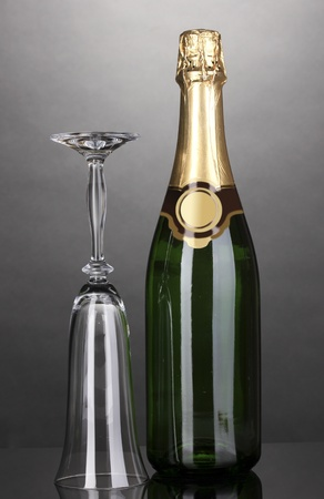 Bottle of champagne and goblet on grey background photo
