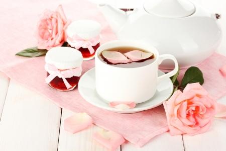 th�i�re et tasse de th� avec des roses et confiture sur la table en bois blanc