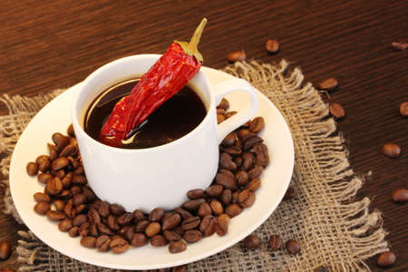 Coffee and pepper on wooden table on brown background photo