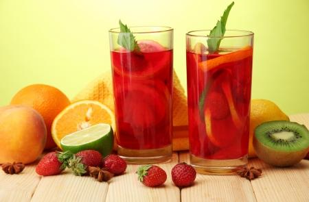 limonada: Refrescante sangr�a en vasos con frutas, sobre la mesa de madera, sobre fondo verde