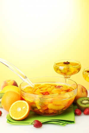 punch in bowl and glasses with fruits, on yellow background photo