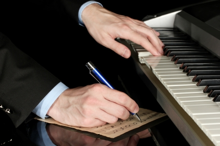 man hands playing piano and writes on parer for notes Stock Photo - 14795096