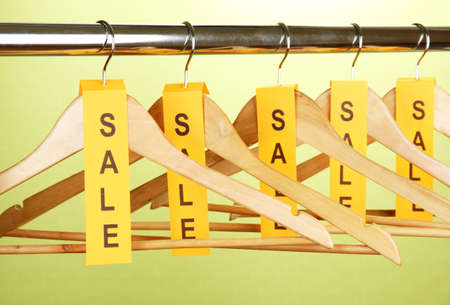 wooden clothes hangers as sale symbol on green background  photo