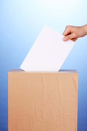 Hand with voting ballot and box on blue background photo