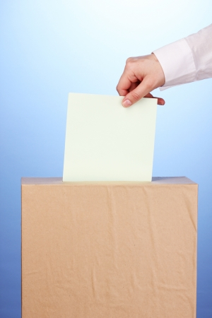 voting ballot: Hand with voting ballot and box on blue background
