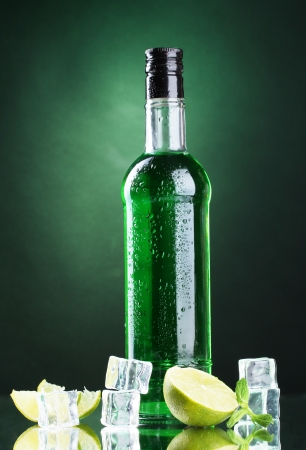 intoxicate: bottle of absinthe with lime and ice on green background