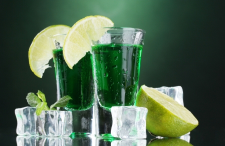 intoxicate: Two glasses of absinthe, lime and ice on green background