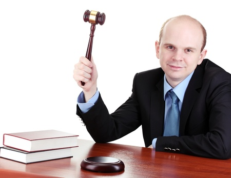 wooden gavel in hand and books on wooden table on gray background photo