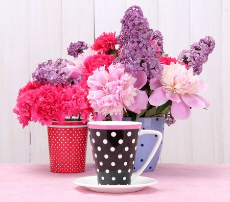 spring flowers and cup on table on white wooden background photo
