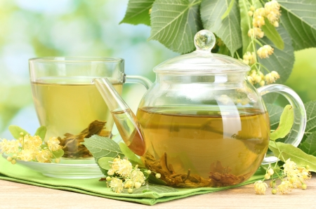 teapot and cup with linden tea and flowers on wooden table in garden Stock Photo - 14836108